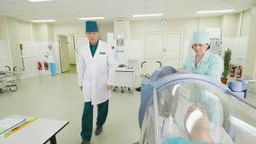 Медсестра кладет персону в соединение проверок доктора томографа сток-видео
