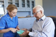 Медсестра помогая старшему человеку организовать лекарство на домашнем посещении стоковая фотография rf