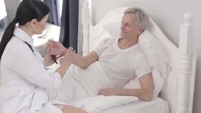 Медсестра рассматривает серого с волосами пациента в его палате VIP видеоматериал