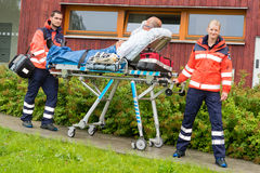 Медсотрудники с пациентом на помощи машины скорой помощи растяжителя стоковые фотографии rf
