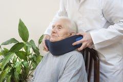 Медсотрудник кладет протезный воротник на шею очень старухи стоковые изображения rf