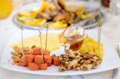 Мед, гайки и сыр славно лежат на плите Сервировка стола стоковые фото