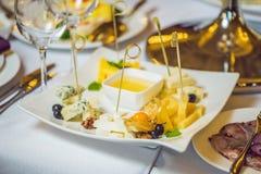 Мед и сыры на белой плите, еда стоковые изображения