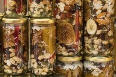 Мед с высушенными плодоовощами и гайками стоковая фотография