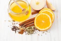 Мед, циннамон, гвоздичные деревья и куски апельсина на белом деревянном столе Стоковые Изображения