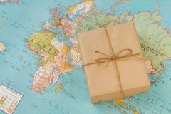 международная перевозка груза Картонная коробка на географическом ба карты Стоковые Фото