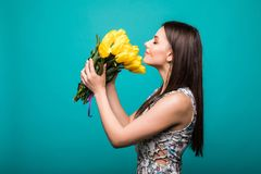 Международные женщины день, марш 8 -го Красивый портрет милой женщины с желтыми тюльпанами в элегантном платье на голубой предпос стоковые изображения