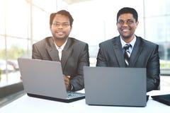 Межрасовая команда дела работая на компьтер-книжке в современном офисе Стоковые Фотографии RF