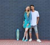 Межрасовые молодые пары в скейтборде whis влюбленности внешнем Сногсшибательный чувственный внешний портрет молодой стильный пред Стоковое Фото