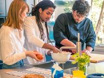Межрасовые пары африканского супруга и кавказской жены подготавливают еду вместе с профессиональным шеф-поваром стоковые изображения