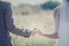 Межрасовые пары держа руки на свадьбе Стоковое фото RF