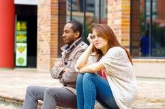 Межрасовые пары осадки сидя на шагах перед зданием, имитируя аргумент для камеры Стоковое Изображение RF