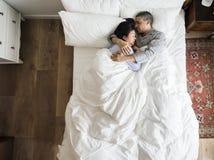 Межрасовые пары спать совместно на кровати стоковое изображение rf