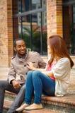 Межрасовые счастливые очаровательные пары сидя на шагах перед зданием взаимодействуя и усмехаясь для камеры Стоковые Изображения RF