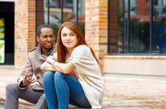 Межрасовые счастливые очаровательные пары сидя на шагах перед зданием взаимодействуя и усмехаясь для камеры Стоковое Изображение