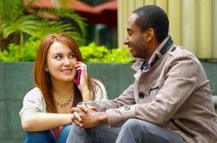 Межрасовые счастливые очаровательные пары сидя на шагах перед зданием взаимодействуя и усмехаясь для камеры Стоковое фото RF