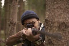 Межрасовый охотник в лесе смотря через бинокулярное Стоковое Изображение