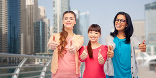 Международные женщины показывая большие пальцы руки вверх в городе Стоковые Изображения