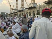 МЕККА, ЖИТЕЛЬ САУДОВСКОЙ АРАВИИ ARABIA-CIRCA ИЮНЬ 2019: Неопознанные мусульманские люди прочитали Коран и предложить молитвы пока стоковое фото