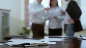 3 менеджера компании обсуждая отчет в конференц-зале, сыгранности на проекте акции видеоматериалы