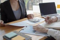 Менеджеры и бухгалтеры проверяли финансы компании Подготовить определение на прошлый 5 год стоковая фотография