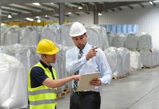 Менеджеры и работники в индустрии снабжения говорят о workin стоковое изображение rf