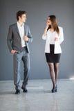Менеджеры укомплектовывают личным составом и женщина говоря друг к другу против предпосылки офиса Стоковое Изображение