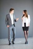 Менеджеры укомплектовывают личным составом и женщина говоря друг к другу против предпосылки офиса Стоковые Изображения