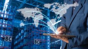 Менеджер бизнесмена используя проверку и управление таблетки для работников с современными торговыми снабжениями склада стоковые фото