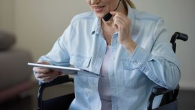 Менеджер в кресло-коляске с шлемофоном разговаривая с клиентом и печатая на таблетке акции видеоматериалы
