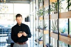 Менеджер в пользе app офиса на мобильном телефоне в современной комнате офиса Стоковая Фотография
