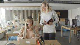 Менеджер женского ментора исполнительный уча женскому интерну объясняя онлайн работу поддержки сток-видео