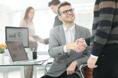 Менеджер и клиент трясут руки встречая в офисе Стоковая Фотография