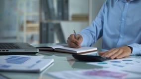 Менеджер компании подсчитывая калькулятор и писать тетрадь, отчет о продажах, проект акции видеоматериалы