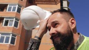 Менеджер конструкции в шлеме с бородой и усик на предпосылке многоэтажного здания 4K видеоматериал