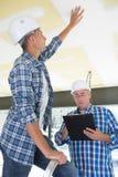 Менеджер конструкции проверяя гипсолит потолка Стоковые Фотографии RF