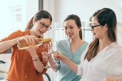 Менеджер льет шампанское для ее сотрудника Стоковые Изображения RF