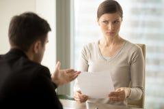 Менеджер пробуя убедить сомнительного женского клиента стоковые изображения rf