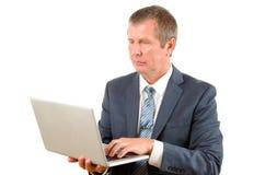 Менеджер программного обеспечения в сюите с компьтер-книжкой в руках на белой предпосылке стоковые фото