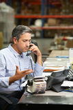 Менеджер работая на столе в пакгаузе Стоковое Фото