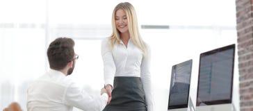 Менеджер рукопожатия с коллегой около настольного компьютера Стоковая Фотография