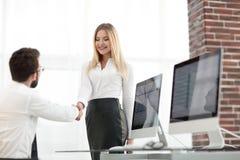 Менеджер рукопожатия с коллегой около настольного компьютера Стоковое фото RF