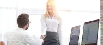 Менеджер рукопожатия с коллегой около настольного компьютера Стоковые Изображения