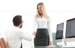 Менеджер рукопожатия с коллегой около настольного компьютера Стоковые Изображения RF