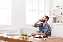 Менеджер сконцентрированный детенышами обсуждает проблему на телефоне в современном белом офисе Стоковые Изображения
