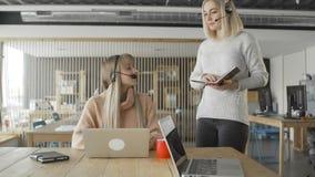 Менеджер с nonebook тренирует нового работника в офисе сток-видео