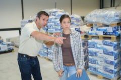 Менеджер хозяйничая вокруг молодого женского работника склада Стоковая Фотография