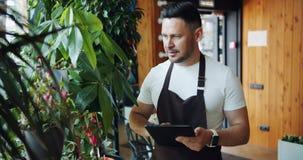 Менеджер цветочного магазина касаясь заводам усмехаясь и используя планшет в работе магазина акции видеоматериалы