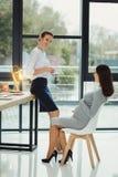 Менеджер HR смотря беременного коллеги и добросердечно усмехаясь Стоковые Изображения