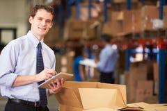 Менеджер в коробках склада проверяя используя таблетку цифров Стоковые Фото